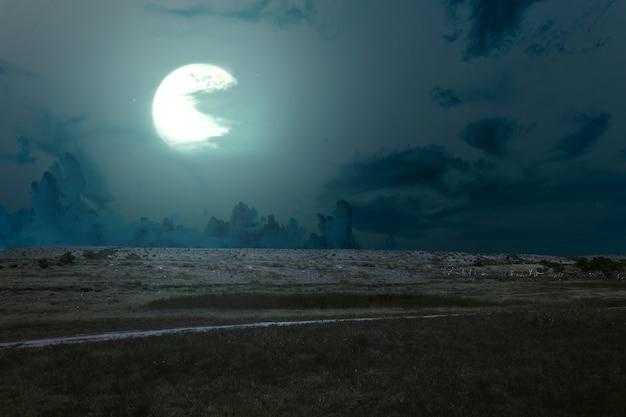 Łąka z chmurami i blaskiem księżyca w nocy