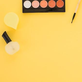 Lakier do paznokci; gąbka i paleta cieni do powiek ułożone w rzędzie na żółtym tle