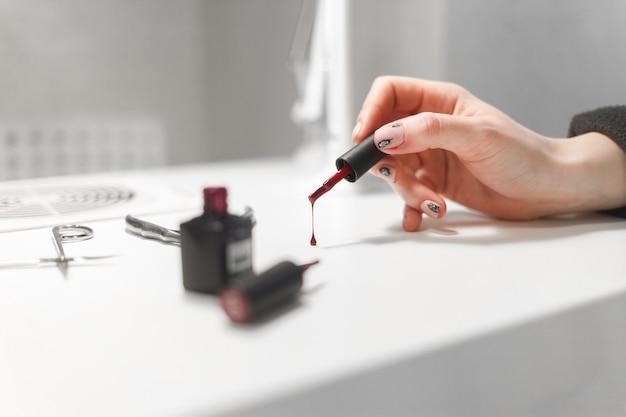 Lakier do paznokci kapie ze pędzla na stół w salonie paznokci