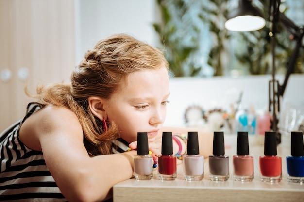 Lakier do paznokci. stylowa atrakcyjna nastolatka siedzi i patrzy na kolory lakieru do paznokci w salonie piękności