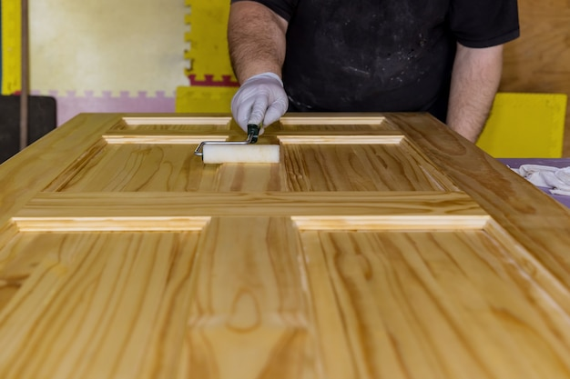 Lakier malarza wykonawcy do malowania nowych drewnianych drzwi wejściowych za pomocą ręcznego lakieru wałkowego z rękawiczkami