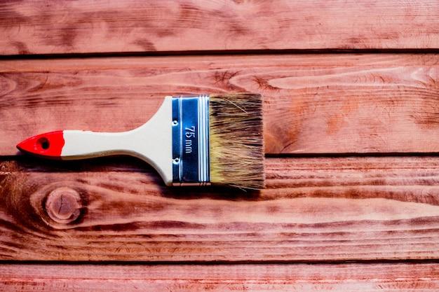 Lakierowanie drewnianej półki za pomocą pędzla. pędzel i farba, plama, drewniana podłoga, ściana, naprawa, koncepcja renowacji. malowanie pędzlem na drewnianym stole do użytku domowego. remont domu skopiuj miejsce