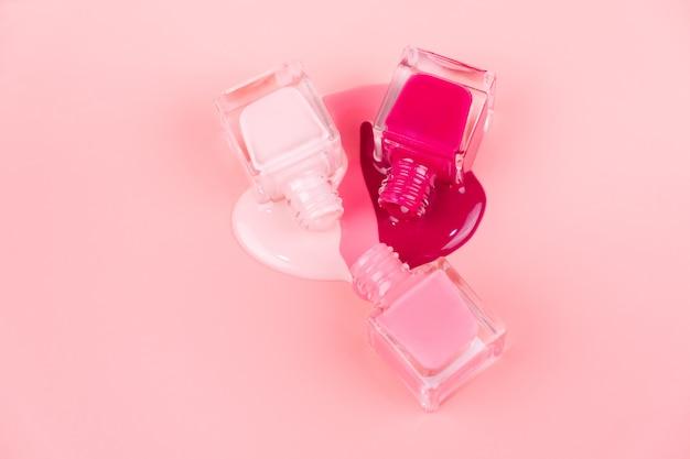 Lakiery do paznokci kapią na różową powierzchnię