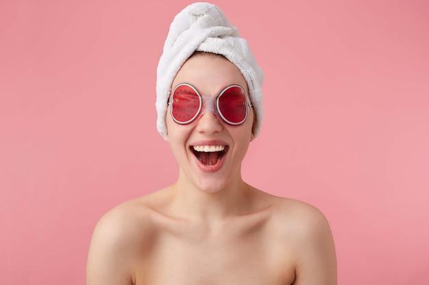 Łał! ale fajnie! młoda szczęśliwa zdumiona kobieta po maseczce spa na oczy iz ręcznikiem na głowie, z szeroko otwartymi ustami i oczami, słyszy fajne wieści, wstaje.