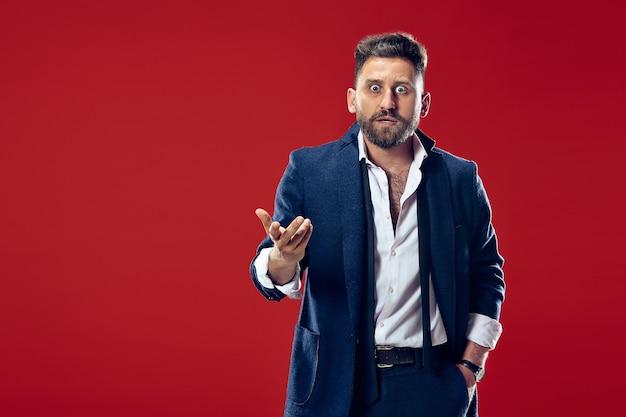 Łał. atrakcyjny męski portret w połowie długości z przodu na czerwonym tle studio. młody emocjonalny zaskoczony brodaty mężczyzna stojący