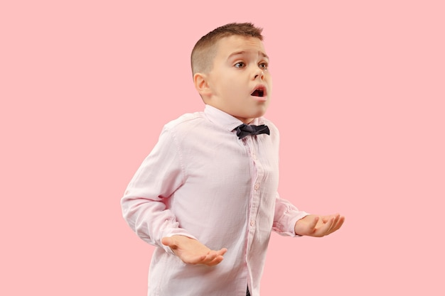 Łał. atrakcyjny męski portret w połowie długości z przodu na różowym tle studio. młody emocjonalny zaskoczony chłopiec nastolatek stojąc z otwartymi ustami. ludzkie emocje, koncepcja wyrazu twarzy. modne kolory