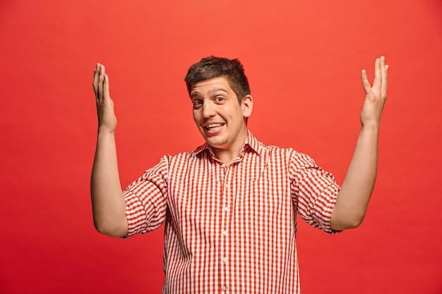Łał. atrakcyjny mężczyzna w połowie długości przedni portret na czerwonym tle studio. młody emocjonalny zaskoczony brodaty mężczyzna stojący z otwartymi ustami.