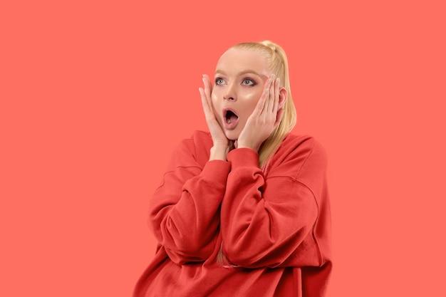 Łał. piękny portret kobiety w połowie długości z przodu na białym tle na koralowym tle studio. młoda emocjonalna zaskoczona kobieta stojąca z otwartymi ustami. ludzkie emocje, koncepcja wyrazu twarzy. modne kolory