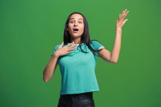 Łał. piękny portret kobiety w połowie długości z przodu na białym tle na zielono. młoda emocjonalna zaskoczona kobieta stojąca z otwartymi ustami