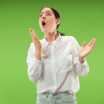 Łał. piękny portret kobiety w połowie długości z przodu na białym tle na zielonym tle studio. młoda emocjonalna zaskoczona kobieta stojąca z otwartymi ustami. ludzkie emocje, koncepcja wyrazu twarzy. modne kolory