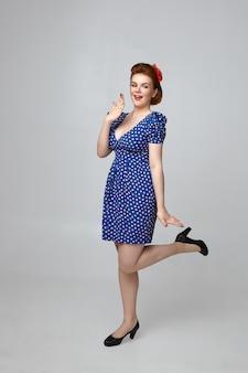 Łał. pionowe zdjęcie atrakcyjnej modnej modelki w stroju retro z lat 60. z podekscytowaną miną, zakrywającą usta i unoszącą nogę. flirty pin up girl pozowanie