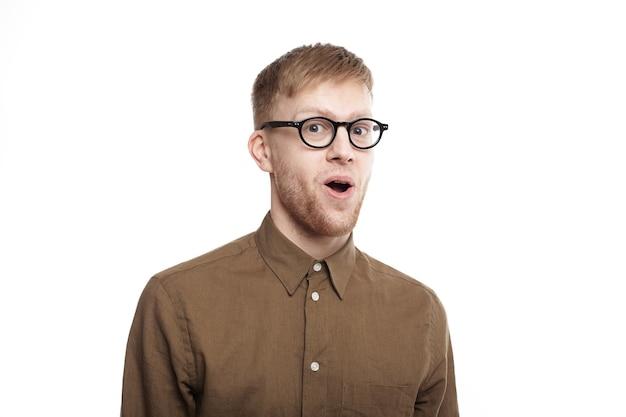 Łał. przystojny, emocjonalny hipster facet w stylowych okularach, wpatrzony w pełne niedowierzanie, unoszący brwi i otwierający usta, z całkowicie zszokowanym wyrazem na owłosionej twarzy