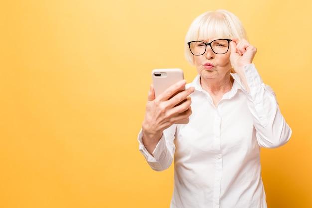 Łał! rozmowa telefoniczna. zdziwiona kobieta w wieku przy użyciu telefonu, odizolowane na żółtym tle.