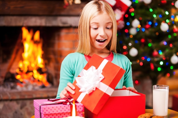 Łał! śliczna dziewczynka otwiera pudełko z prezentami i uśmiecha się siedząc przy stole z choinką i kominkiem w tle