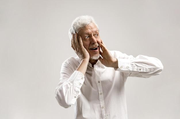 Łał. starszy mężczyzna w połowie długości portret na szarej ścianie. dojrzały brodaty mężczyzna z otwartymi ustami. ludzkie emocje, koncepcja wyrazu twarzy. modne kolory