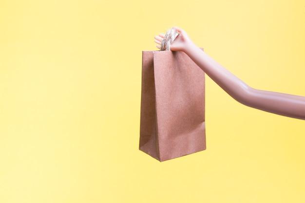 Lalka trzyma małą papierową torbę