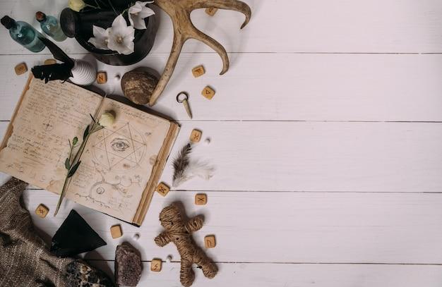 Lalka voodoo wykonana ze sznurka leży ze starym grymuarem książkowym, otoczona magicznymi przedmiotami rytuału, płasko leżąca