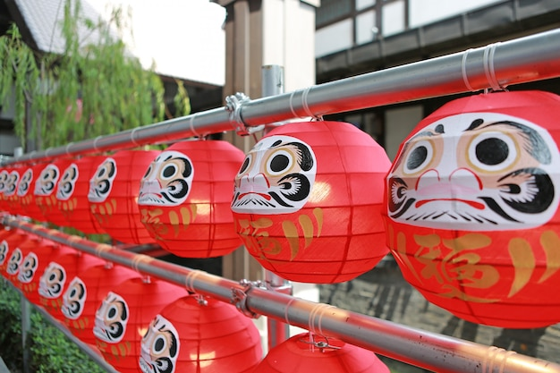 Lalki daruma. symboliczne japońskie lalki wiszące w rzędzie.