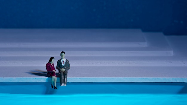Lalki siedzą obok basenu z miejsca na kopię