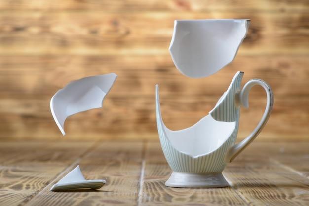 Łamająca rocznik porcelanowa filiżanka na drewnianym stole