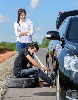 Łamana kołowa mężczyzna zmienia oponę pomaga żeńskim przyjaciołom