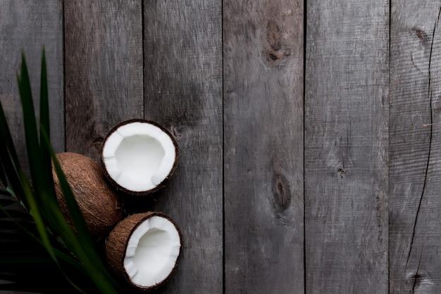 Łamane kokosy na szarym tle drewnianych z liściem palmowym. miazga z białego kokosa. wysokiej jakości zdjęcie