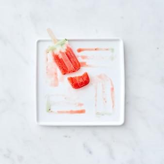 Łamane lody owocowe na patyku na białym talerzu z wzorem z rozmrażających lodów na szarym marmurowym tle. skopiuj miejsce na tekst. leżał na płasko