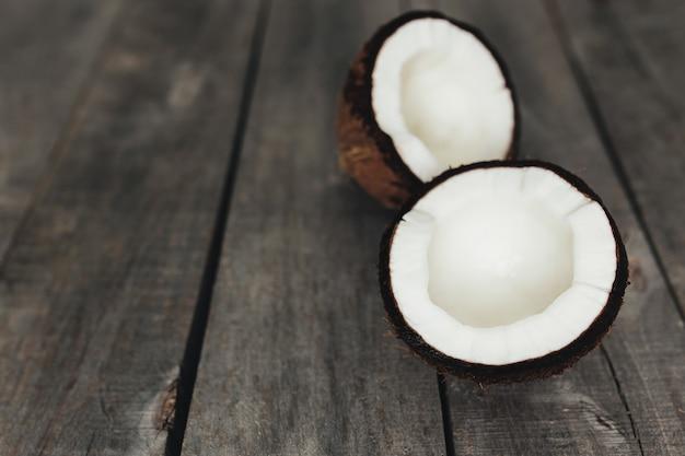Łamane orzechy kokosowe na szarym tle drewnianych. miazga z białego kokosa. wysokiej jakości zdjęcie