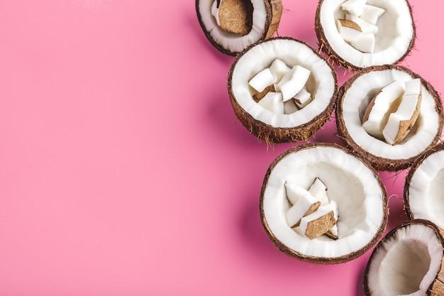 Łamani kokosów kawałki na jaskrawym różowym tle, odgórny widok, kopii przestrzeń