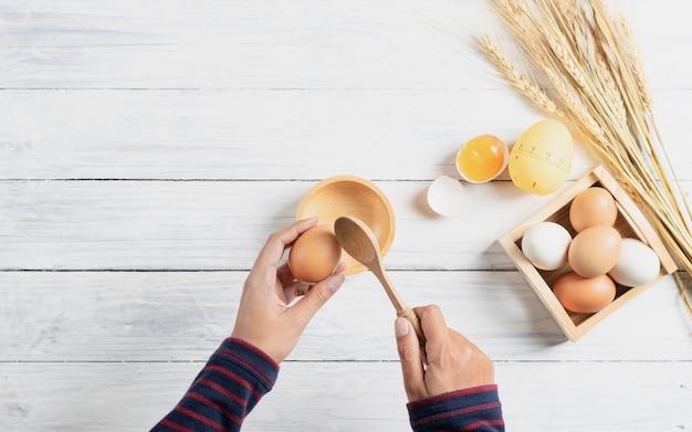 Łamanie gotowany jajko z drewnianym łyżkowym dorp w drewnianym pucharze