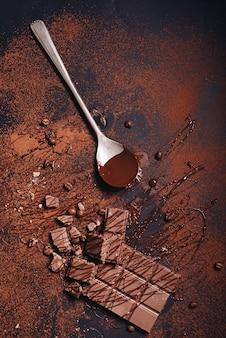 Łamany baton czekoladowy i syrop na zapylonym proszku kawowym