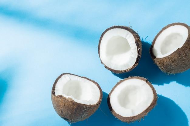 Łamany kokos na niebieskiej powierzchni w naturalnym świetle z cieniami. ostre światło. pojęcie diety, zdrowe odżywianie, odpoczynek w tropikach, wakacje i podróże, witaminy.