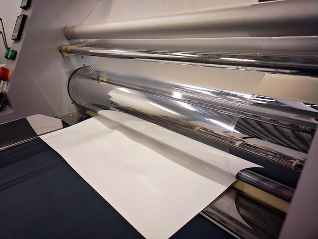 Laminator przemysłowy, laminowanie wyrobów papierniczych. produkcja opakowań. przestarzały sprzęt. firma. miejsce na tekst.