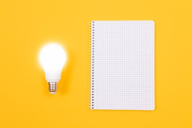 Lampa energooszczędna i notatnik na żółtym stole
