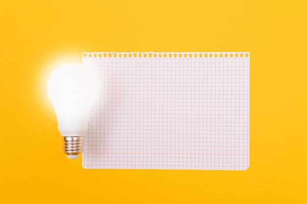 Lampa energooszczędna z notatnikiem leżąca na żółtym stole