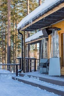 Lampa grzewcza umieszczona wśród stołów otwartej kawiarni zimą w ciągu dnia