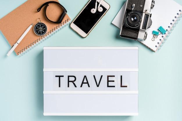 """Lampa led z literą """"travel"""". tło turystyki. widok z góry na podróż i akcesoria biznesowe"""