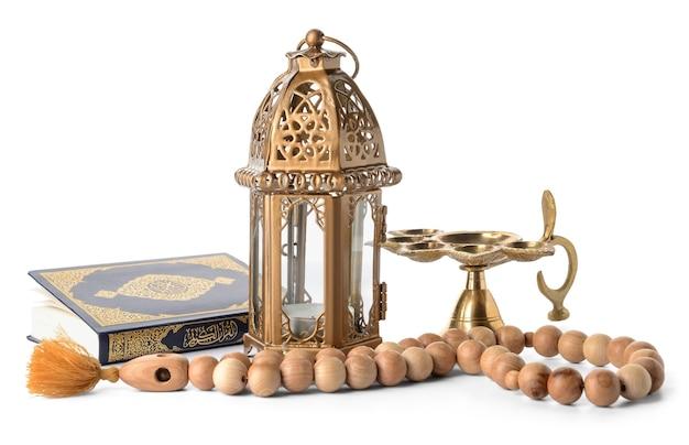 Lampa muzułmańska, tasbih i koran na białym tle