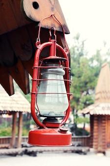 Lampa naftowa wisząca na drewnianym domu, na zewnątrz