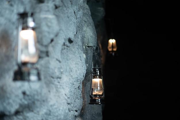 Lampa naftowa wisząca na kamiennej ścianie jaskini