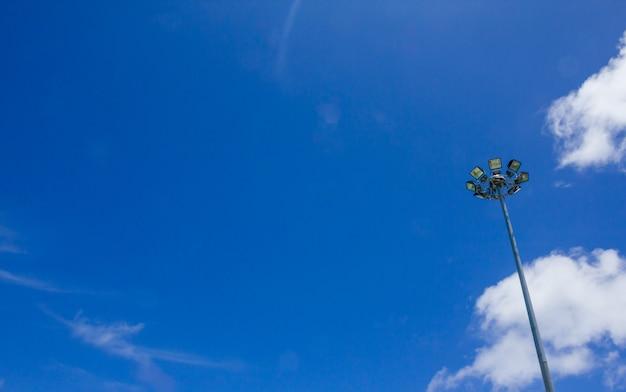 Lampa oświetleniowa na słupie na tle błękitnego nieba, sport światło z niebieskim tle chmur nieba