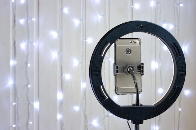 Lampa pierścieniowa i smartfon na statywie na świątecznym tle.