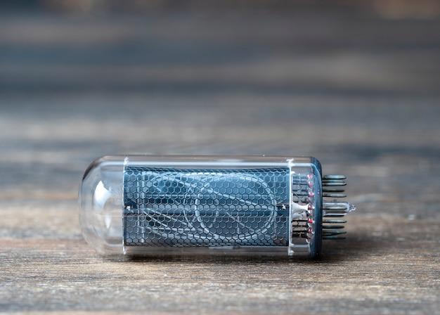 Lampa próżniowa retro na drewnianym tle, zbliżenie, wskaźnik rurki nixie. wskaźnik wyładowania jarzeniowego