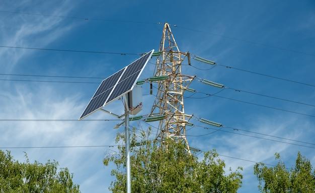 Lampa uliczna na bateriach z panelu słonecznego na tle wieży wysokiego napięcia