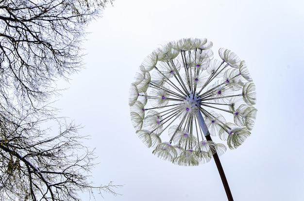 Lampa uliczna w kształcie mniszka lekarskiego pochmurnego zimowego nieba i gałęzi drzew. oryginalne, nietypowe konstrukcje oświetleniowe. jak natura odbija się w ludzkich kreacjach technologicznych