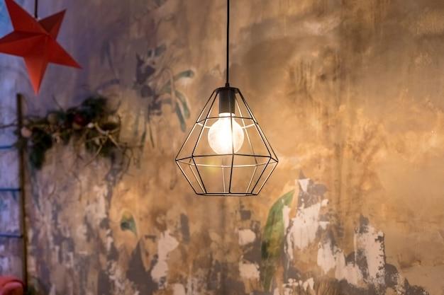Lampa wisząca w kształcie abażuru w kształcie geometrycznym, złoty metalowy żyrandol. zaprojektuj strych. przemysłowy styl. żarówki w ciemności. światła i ciemne tło. oświetlenie wnętrza w stylu miejskim z abażurami klatkowymi