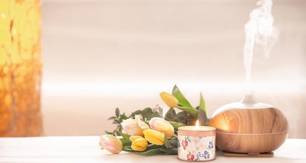 Lampa z dyfuzorem olejku aromatycznego na stole na rozmytym tle z pięknym wiosennym bukietem tulipanów i płonącą świecą.
