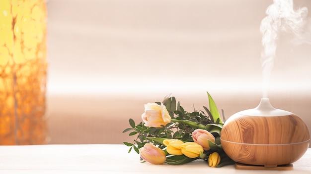 Lampa z dyfuzorem olejku zapachowego na stole na rozmytym tle z pięknym wiosennym bukietem tulipanów.