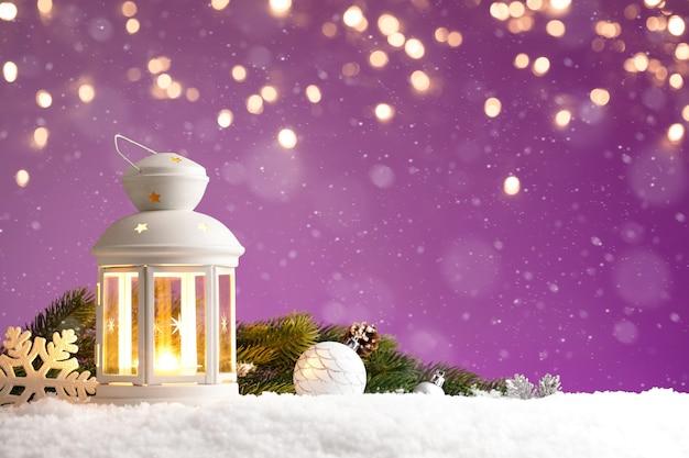 Lampion bożonarodzeniowy z dekoracjami na fioletowym tle ze złotymi światłami