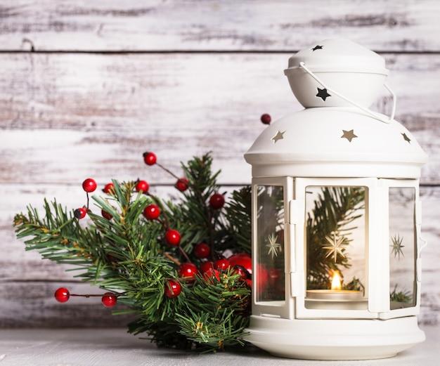 Lampion cristmas z jodłą i jagodami na odrapanym drewnianym tle